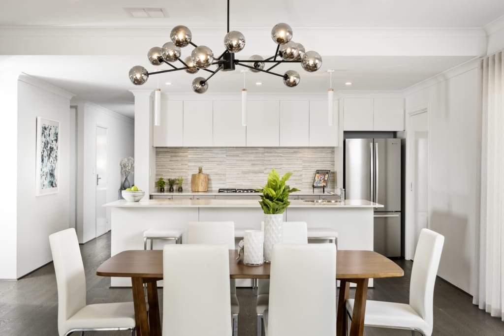 Dining room and kitchen staged with leather chairs, wooden table, contemporary light bulbs